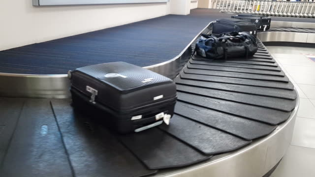 conveyor belt in arrivals lounge at the airport - luggage stock videos & royalty-free footage