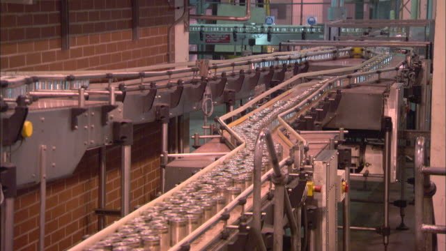 a conveyor belt moves cans of soup through a factory. - 缶詰にする点の映像素材/bロール