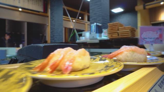 conveyor belt rotated sushi 4k - shrimp seafood stock videos & royalty-free footage