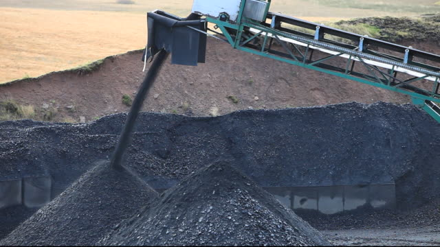 a conveyor belt that takes coal from the glentaggart open cast coal mine to a road head for onward transport by road in lanarkshire, scotland, uk. as well as the disastrous climate change consequences of continuing to mine and burn coal, living close to op - fossil fuel stock videos and b-roll footage