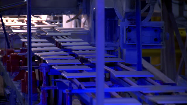 a conveyor moves ceramic tiles past an ultra violet inspection device. - uv protection stock videos and b-roll footage