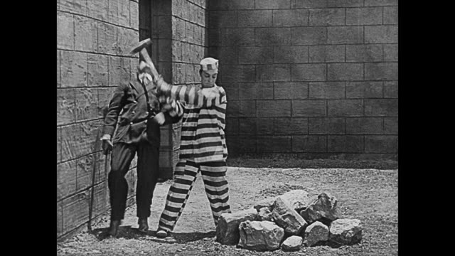 1920 a convict (buster keaton) breaks rocks and knocks out prison guard - prison wall stock videos & royalty-free footage