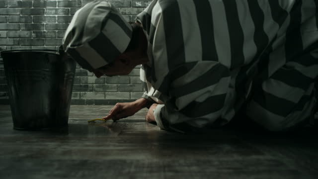 Convict cleaning floor of prison cell with toothbrush in correctional institution