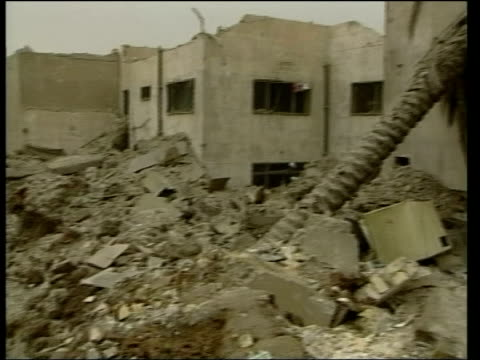 vídeos de stock, filmes e b-roll de convoy attack may have targetted saddam itn rubble of building attacked after intelligence that it was being used by saddam pan ms rubble being... - 2003