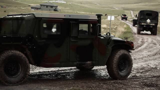 convoy driving by on muddy road, with gun fire. - army stock-videos und b-roll-filmmaterial