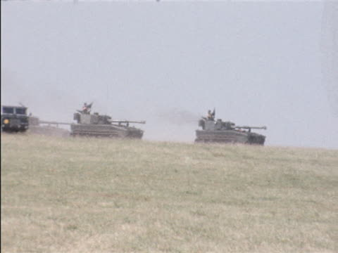 A convoy of Abbot combat vehicles drive across Salisbury Plain during a NATO training exercise