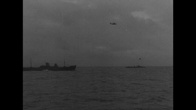 vidéos et rushes de convoy of american destroyers en route to england / mls two destroyers headed out to sea / airplane flying above destroyers / mls bow of ship cutting... - marin
