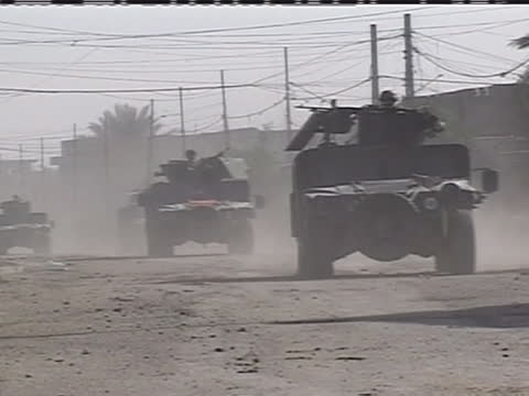 convoy of army humvee's drive down a dusty street in iraq. - (war or terrorism or election or government or illness or news event or speech or politics or politician or conflict or military or extreme weather or business or economy) and not usa stock videos & royalty-free footage