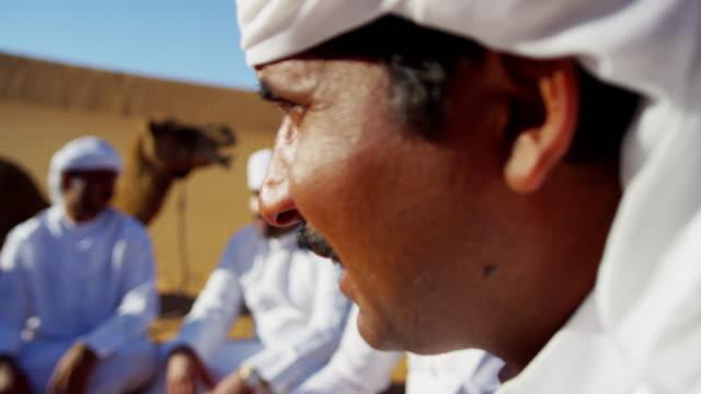 vídeos de stock, filmes e b-roll de convoy of camels with owners travelling saudi desert - adereço de cabeça