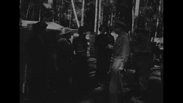a convoy of jeeps drives on a dirt road past numerous new guinean natives / gen douglas macarthur leans on a cane and holds a cigar as he talks to... - general macarthur stock videos & royalty-free footage