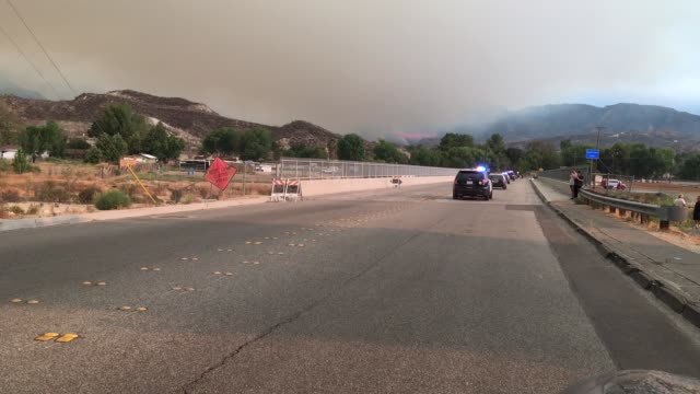 a convoy of police while firefighting helicopters refill water as firefighters continue to battle the sand fire near santa clarita ca july 23 2016 - santa clarita video stock e b–roll