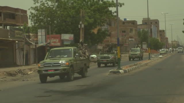 a convoy of rapid support forces militia trucks driving through khartoum sudan - convoy trucks stock videos and b-roll footage