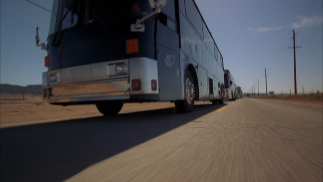 WS LA REAR POV Convoy of semi trailer trucks and large tour buses traveling on highway toward camera