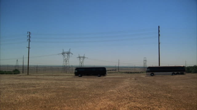 WS Convoy of semi trailer trucks and large tour buses traveling through rural area