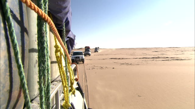 a convoy of sport utility vehicles passes through a desert. - konvoi stock-videos und b-roll-filmmaterial
