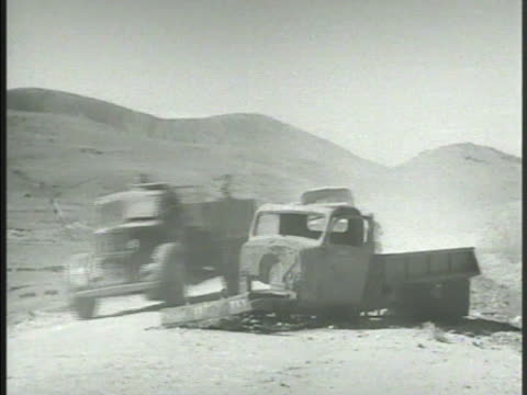 stockvideo's en b-roll-footage met convoy of trucks on mountain road. trucks passing wrecked truck. trucks entering village . road sign ''this is the last taverna...' greek civil war - 40 seconds or greater