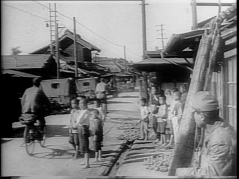 convoy of us army jeeps driving down road in japan / view of street sign reading 'to nikko' / jeeps driving past civilians in japanese village /... - pacific war video stock e b–roll