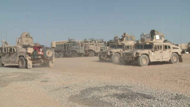 A convoy of U.S. Marine Humvees departs from a staging area.