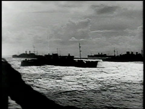 convoy of us ships in silhouette on unidentified body of water pan behind soldier standing by railing looking out at ships - anno 1942 video stock e b–roll
