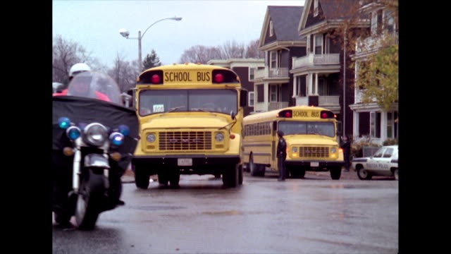 convoy of yellow school buses drive along a road in boston towards the camera and pass by out of shot during the desegregation bussing crises; 1974. - 1974 stock videos & royalty-free footage