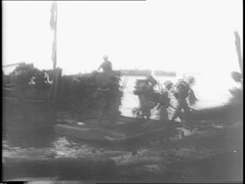 vídeos de stock e filmes b-roll de convoy / soldier wearing helmet on ship / map of pacific islands / ship fires gun / explosion in water / smoke screen near shore / soldiers loading... - enfeites para a cabeça