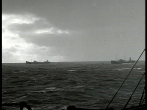 convoy turbulent seas atlantic ocean. vs sailors on bridge of ship look out binoculars telescope. int naval officers charting course on map. man at... - 大西洋点の映像素材/bロール