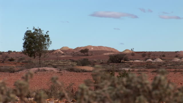 ws coober pedy mining mounts with brush in foreground, coober pedy, south australia, australia - coober pedy stock videos & royalty-free footage