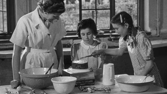 1950 montage a cook and child observe a young girl putting icing on a cake with the remnants of cake baking on the island before them / united kingdom - 1950 stock videos and b-roll footage