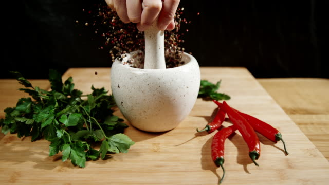 slo mo cook cracking peppercorns - mortar and pestle stock videos and b-roll footage