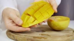 A cook cuts a juicy ripe mango. Close-up
