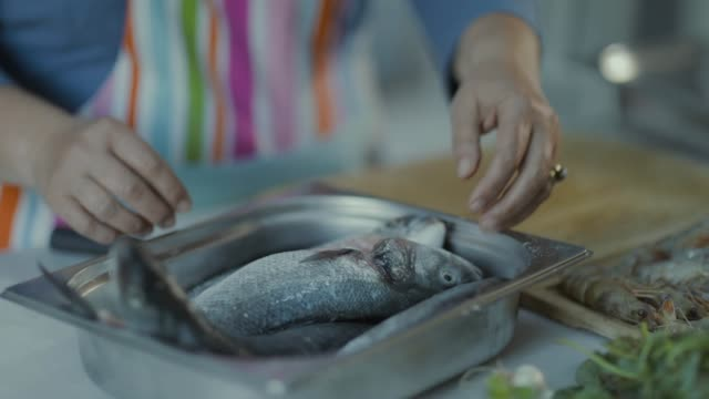cook cuts the fish on table - organic stock videos & royalty-free footage