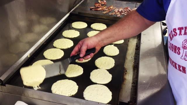 vídeos de stock, filmes e b-roll de cook flips pankcakes on griddle - espátula