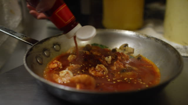 cook in restaurant adds ingredients to shrimp and sauces in pan and carries them to a commercial range in a restaurant - ketchup stock videos and b-roll footage
