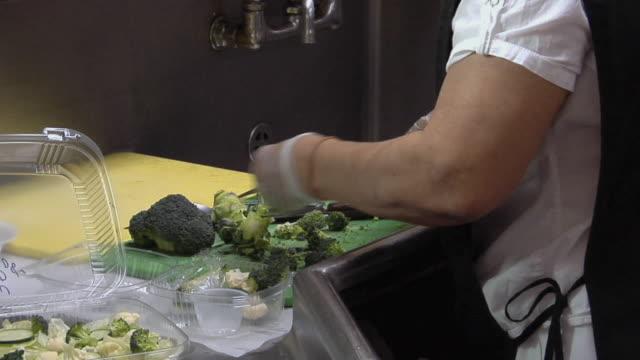 vídeos de stock e filmes b-roll de cu zo ms cook in school kitchen adding broccoli to salads / belleville, michigan, usa - merenda escolar