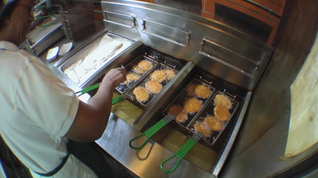 MS HA Cook in school kitchen checking on chicken patties cooking in oil / Belleville, Michigan, USA