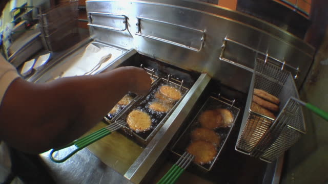 ms cook in school kitchen checking on chicken patties cooking in oil / belleville, michigan, usa - unhealthy eating stock videos & royalty-free footage
