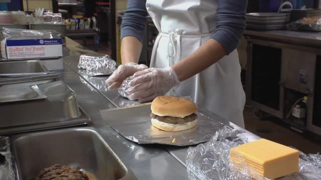 MS Cook in school kitchen preparing chicken sandwiches / Belleville, Michigan, USA