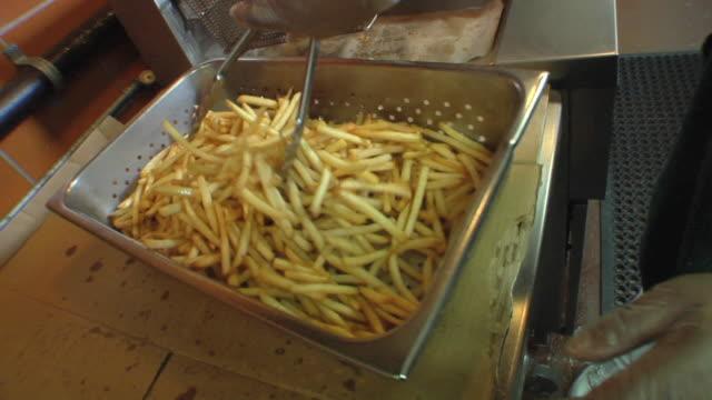 vídeos de stock e filmes b-roll de cu cook in school kitchen preparing french fries / belleville, michigan, usa - merenda escolar