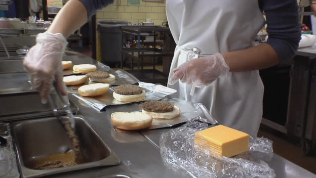 ms cook in school kitchen preparing hamburgers with cheese slices / belleville, michigan, usa - kantine stock-videos und b-roll-filmmaterial