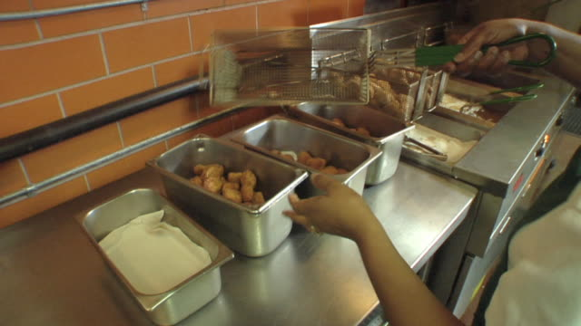 ms cook in school kitchen removing chicken pieces from oil and placing them in containers / belleville, michigan, usa - unhealthy eating stock videos & royalty-free footage