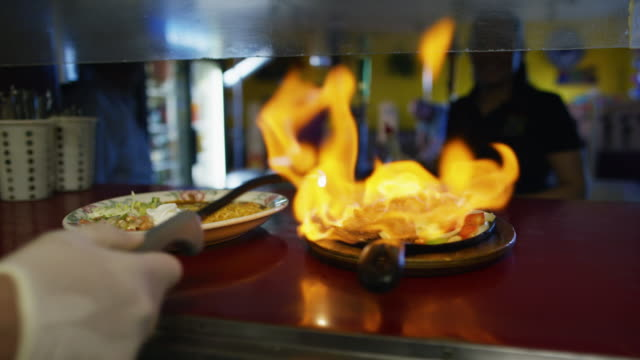 a cook lights a plate of fajitas (flambe) in a serving window as a female server walks up at a mexican restaurant - mexican culture stock videos & royalty-free footage