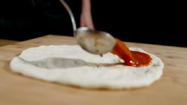 slo mo cook pouring tomato sauce over pizza dough - preparation stock videos & royalty-free footage
