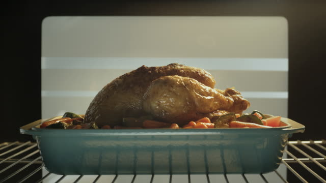 a cook pours basting juices over a roasting chicken. - oven stock videos & royalty-free footage