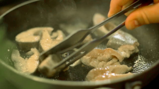 cook puts the fillet of fish on the frying pan, slo mo - branch plant part stock videos & royalty-free footage