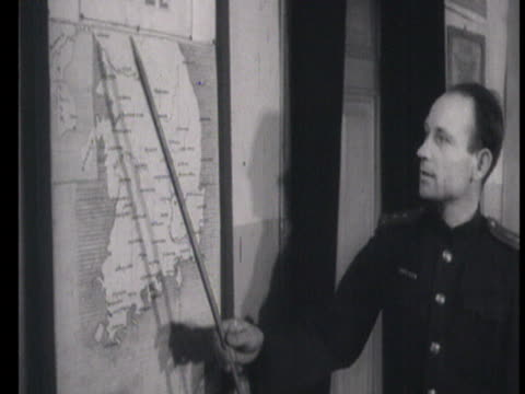 Cook putting bread on table guards studying map of battles in Korean War / Russia AUDIO