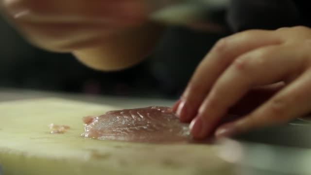 vidéos et rushes de cook removing spins from a fish - seulement des jeunes hommes
