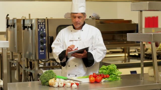 Cook taking notes with a tablet pc in a kitchen