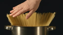 A cook touches a bunch of a spaghetti in a steel pot