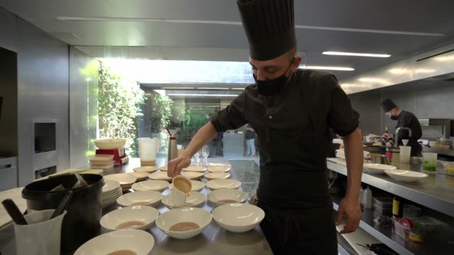 cook, wearing a protective mask, prepares dishes of the tasting menu at 'les cols' restaurant on june 24, 2020 in olot, girona, spain. 'les cols' has... - table stock videos & royalty-free footage
