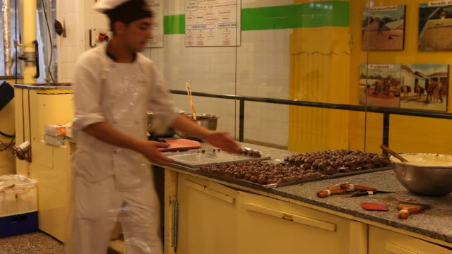 A cook with a protective cap keeps chocolate chocolates on his tray in the chocolate factory 'Del Turista' in Bariloche in Patagonia